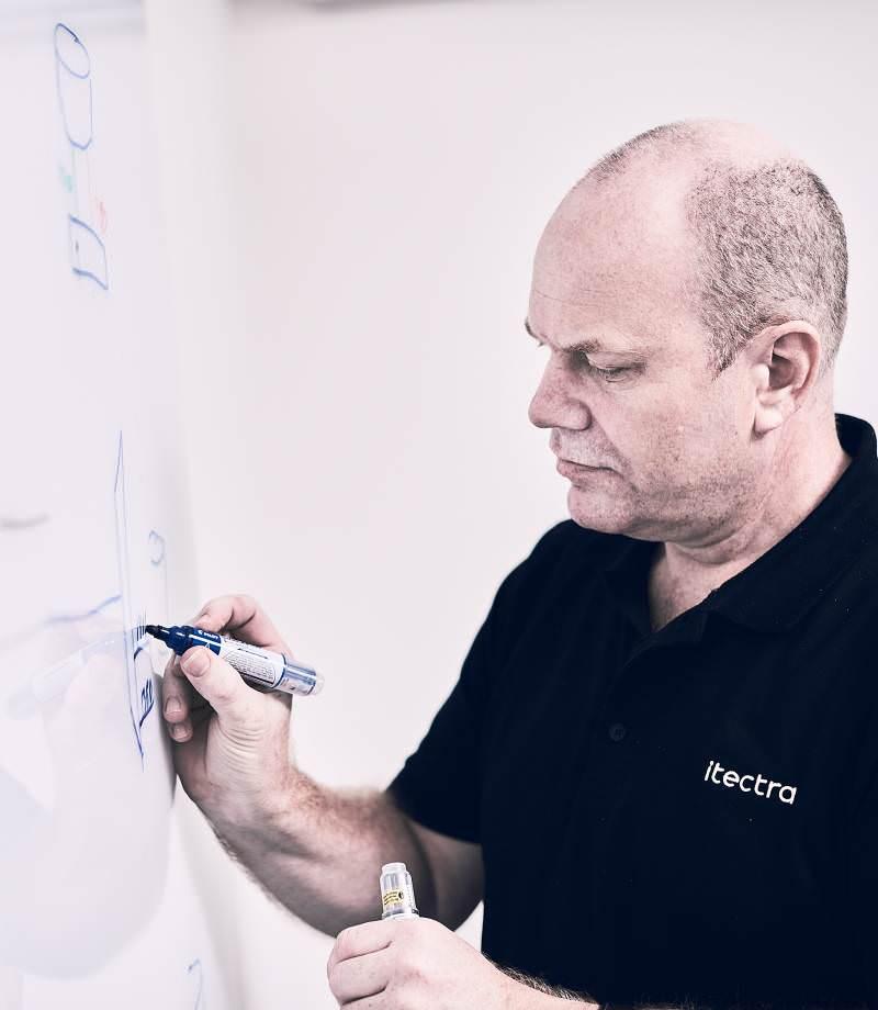 Mandlig medarbejder ved tavle tegner elementer til it infrastruktur