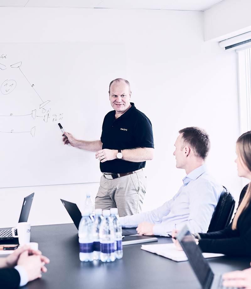 Medarbejder-møde i Itectras lokaler. En medarbejder tegner og deler sin viden om it infrastruktur og Itectra Services med sine kollegaer.