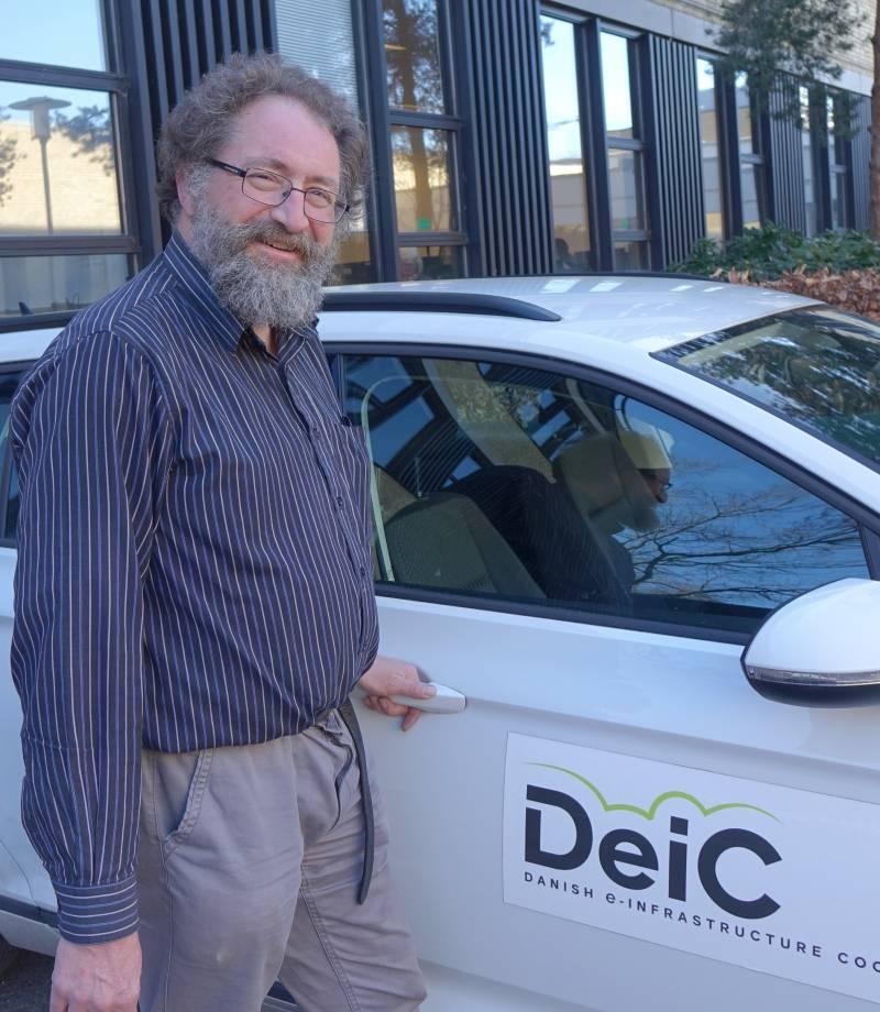 Medarbejder fra DeiC foran en firmabil.